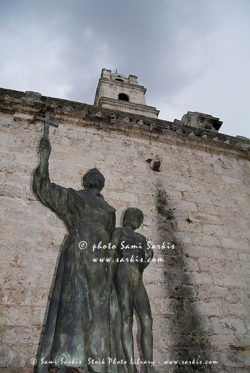 Statue of San Francisco de Asis on a brick wall near the convent on Plaza de San Francisco, Havana Cuba.