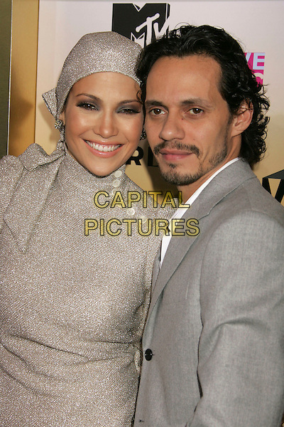 JENNIFER LOPEZ & MARC ANTHONY.Arrivals - 2006 MTV Video Music Awards held at Radio City Music Hall, New York City, New York, USA,.31 August 2006..half length silver sparkly glittery long sleeved sleeves  dress grey retro hat head scarf married husband wife couple buttons collar bow .Ref: ADM/RE.www.capitalpictures.com.sales@capitalpictures.com.©Russ Elliot/AdMedia/Capital Pictures.