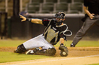 Kannapolis Intimidators catcher Michael Marjama (12) slides to stop a throw at home plate during the South Atlantic League game against the Lakewood BlueClaws at CMC-Northeast Stadium on August 13, 2013 in Kannapolis, North Carolina.  The Intimidators defeated the BlueClaws 12-8.  (Brian Westerholt/Four Seam Images)