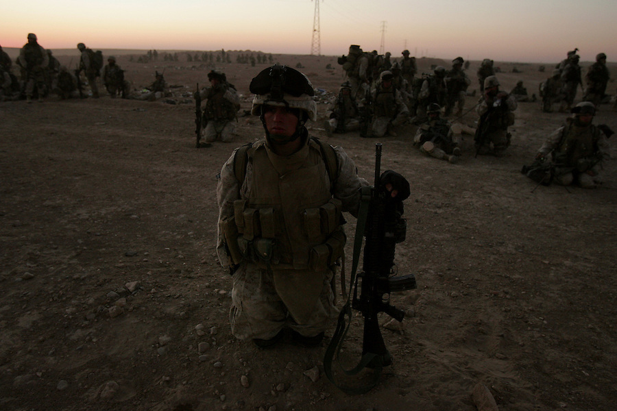 Marines with Golf Co. 2nd Battalion 1st Marines wait to move from their attack positions in a pre-dawn sweep into the Iraqi-Syrian border town of Ubaydi as part of Operation Steel Curtain on Tues. Nov. 14, 2005.