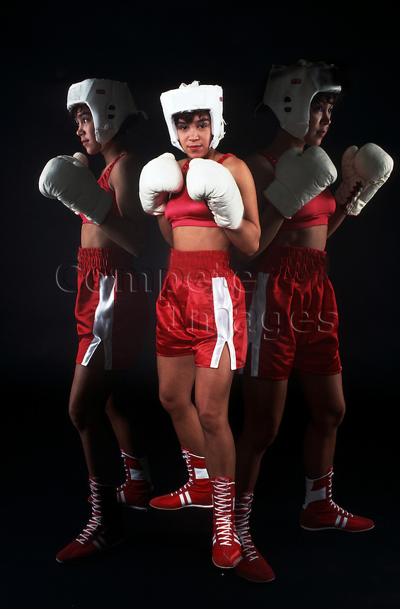 Woman wearing boxing gloves and head protection