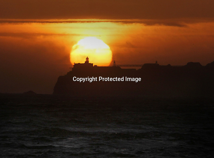 The sunsets behind Point Bonita Point lighthouse as seen from San Francisco's Baker Beach.