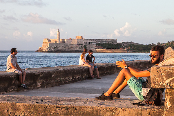 Relaxing on the Malecón in late afternoon, with Morro Castle and the harbor entrance in the distance, Centro Habana