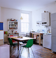 This low-key kitchen is furnished with an assortment of collected furniture and appliances
