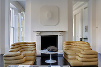 A pair of tiered modular leather sofas in the living room are by Ubald Klug for De Sede and the artwork above the fireplace is by Turi Simeti