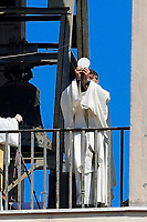 Rome April 12th 2020. Due to the coronavirus emergency, Easter celebrations are forbidden all over Italy. Don Maurizio Mirilli, a catholic priest of the church of Santissimo Sacramento, situated in south-east part of Rome, celebrates the mass from the bell tower while the faithfuls follow the mass from balconies.<br /> Photo Samantha Zucchi Insidefoto