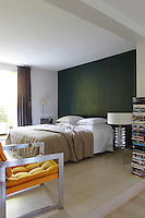 A signature wall in the master bedroom has been painted a dark green and the room is furnished with a 1970s lamp and armchair