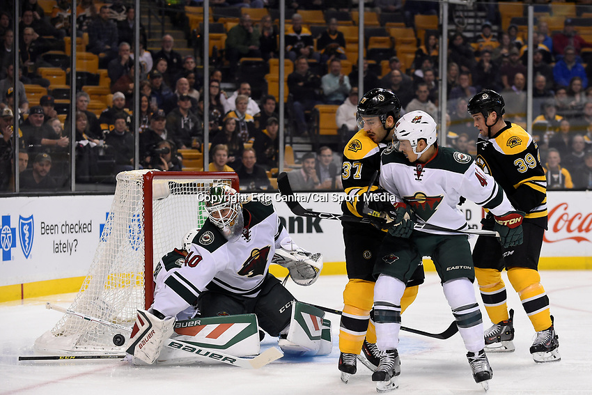 Thursday, November 19, 2015: Minnesota Wild goalie Devan Dubnyk (40) makes a save as Boston Bruins center Patrice Bergeron (37) and defenseman Jared Spurgeon (46) battle in front of the net during the National Hockey League game between the Minnesota Wild and the Boston Bruins held at TD Garden, in Boston, Massachusetts. Eric Canha/CSM