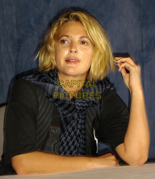 "DREW BARRYMORE.Press Conference for ""Whip It"" at the Andaz Hotel in Hollywood, California, USA..September 29th, 2009.half length black grey gray pinstripe top hand touching hair pattern scarf .CAP/AW.©Anita Weber/Capital Pictures."