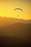 A paraglider soars over hazy ridgelines at sunset in Jackson Hole, Wyoming.