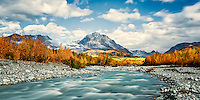 Sun breaking it's way through clouds to light up autumn colors on Granite Creek on Gelnn Highway Alaska