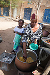 A woman sells fried plantains (alloco) and potatoes for breakfast next to the bus station in Segou, Mali.