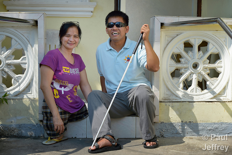 In Abucay, a seaside town in the Philippines province of Bataan, Ellen Bundang sits on the front step of her home talking with Dennis Garcia, president of the Abucay Federation of People With Disabilities (PWDAF). Born with abnormal legs, Bundang is a member of the PWDAF. Garcia is blind.