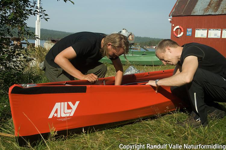 To menn monterer Ally kano ved Femunden. ---- Two men and Ally canoe.