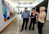 STAFF PHOTO BEN GOFF  @NWABenGoff -- 07/18/14 Heidi Carlsen-Rogers of Bella Vista, from right, talks about the paintings in her 'Connecting the Dots' exhibit with friend Becky Ford and husband Jim Ford, of Garfield, during the grand opening of STORY: The Galley at Grace Point at Grace Point Church in Bentonville on Friday July 18, 2014.