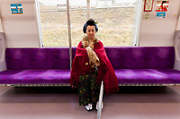 A geisha wearing kimono travelling on a train in suburban Tokyo. Japan. Sunday December 23rd 2018