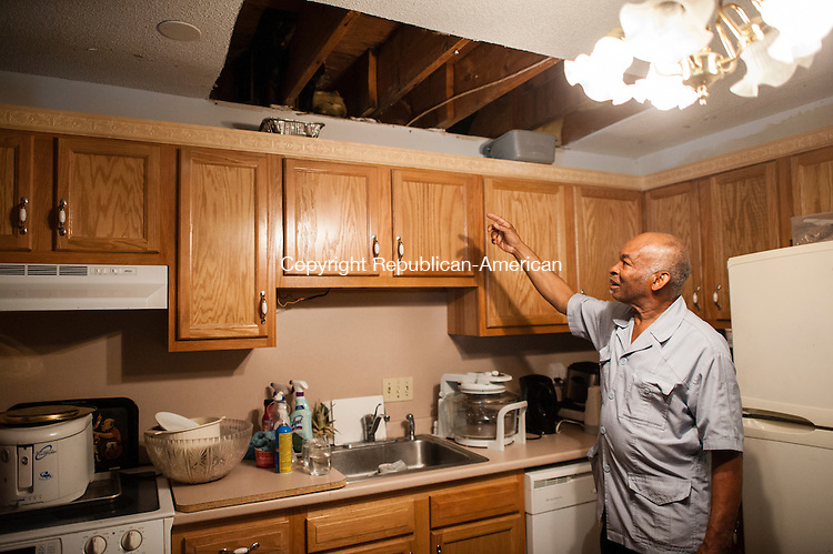WATERBURY, CT-17 June 2014-061714EC04-  Jonathan Hutchinson points to a hole in his kitchen ceiling. He says contractors have not been at his condo since February, after they ripped down walls and started repairs from ongoing flooding damage. Several residents who live at the Bradley Gardens housing complex in Waterbury are upset that their units have been left with construction work to be completed. Despite repeated attempts, they have not heard from the management company. Erin Covey Republican-American