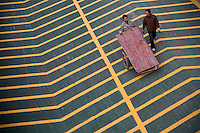 Workers transport construction materials down a parking garage ramp in Xianlin district of Nanjing, Jiangsu, China.