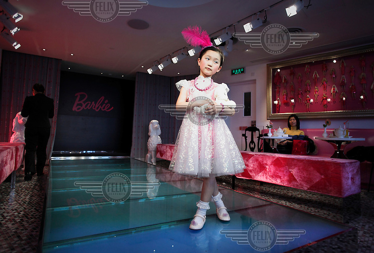 A young girl wearing a flouncy pink dress and made-up, poses on a cat walk at the opening of a flagship Barbie store. The inauguration of the building was timed to coincide with the 50th anniversary of the doll's first ever sale.