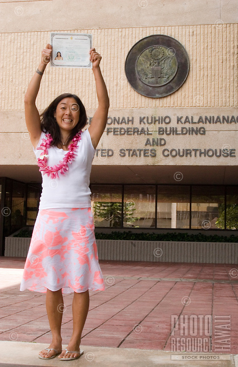 Young Japanese-American woman proudly displays American citizenship document at Honolulu courthouse naturalization ceremony