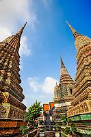 Upward view of chedis including distant Phra Si Sanphet Chedi, Wat Pho, Bangkok, Thailand