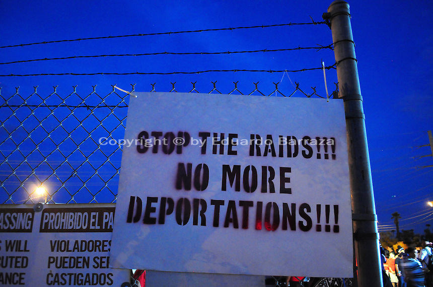 """Phoenix, Arizona. September 22, 2012 - A poster against immigration raids and deportations of undocumented immigrants in Arizona and elsewhere in the United States is seen on display on the fence of the lot where the """"Festival of Resistance"""" was held. Photo by Eduardo Barraza © 2012"""