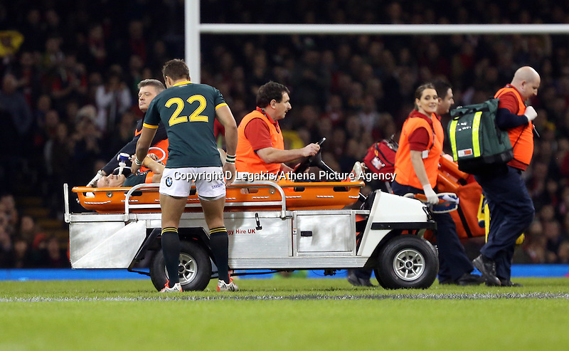 Pictured: Handre Pollard (22) speaks to injured team mate Jean de Villiers of South Africa as he is transferred away after dislocating his knee Saturday 29 November 2014<br /> Re: Dove Men Series 2014 rugby, Wales v South Africa at the Millennium Stadium, Cardiff, south Wales, UK.