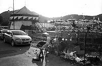 Festival di trombe e ottoni di Guca (Cacak). Un uomo rovista tra la spazzatura dietro al parco divertimenti --- Trumpet festival of Guca (Cacak). A man rummages in the garbage behind the amusement park