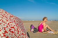 Senior woman reading a magazine at the beach, Camargue, France.