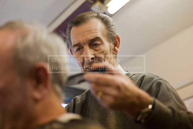 With years of experience etched on his face, Mike sets to work cutting the hair of one of his regular customers.