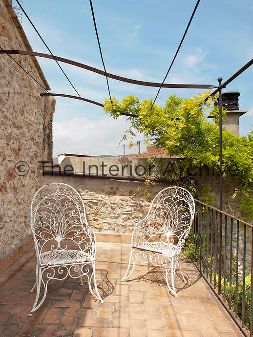 A pair of white wrought iron chairs on the terrace covered with a simple pergola