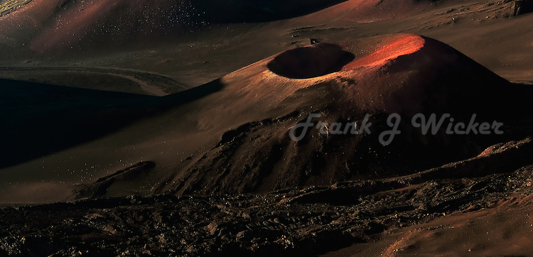 The warm glow of sunrise highlight the lava flows of this cinder in HALEAKALA NATIONAL PARK on Maui in Hawaii