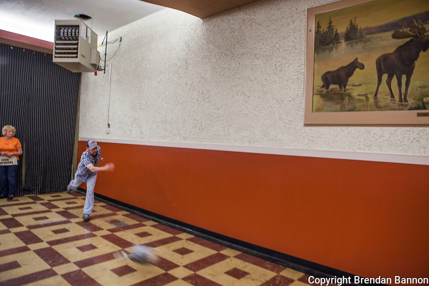 A particpant takes aim with a duct taped frozen turkey during a turkey bowling session at a meat raffle at the Moose Lodge in lancaster, NY. Meat raffles have become popular fundraisers in Western New York. April 2016. Lancaster, NY. Photo by Brendan Bannon
