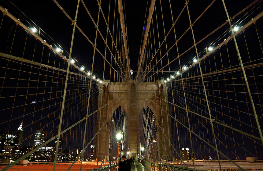 A couple kiss at night on the Brooklyn Bridge in New York City, New York