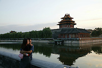 A young couple hug together by the moat of the Forbidden City in Beijing, China..