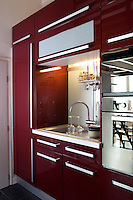 The sink is located beside the oven along one wall of this kitchen, surrounded by a built-in storage unit in a burgundy lacquer finish