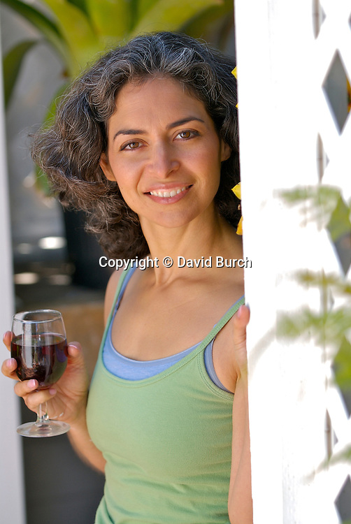 Mature woman holding wineglass, smiling