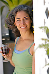 Mature woman holding wineglass, smiling