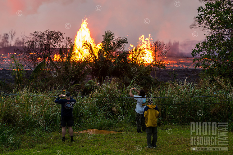 June 2018: Three people take photos of the Kilauea Volcano eruption in Leilani Estates, Puna district, Big Island of Hawai'i.