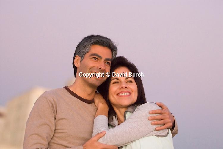 Hispanic couple with arms around at sunset