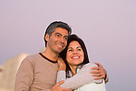 Hispanic couple with arms around at sunset