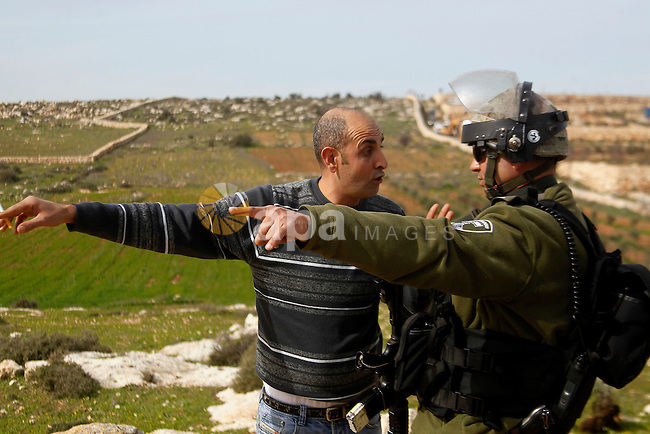 A Palestinian man argues with Israeli soldiers during the demolition of a Palestinian house at the order of the Israeli army as he tries to stop the demolition in the West Bank village of Biet Ula, west of Hebron January 21, 2016. The owners of the house said they were informed by the Israeli army that the demolition was carried out because they did not have an Israeli-issued construction permit. Photo by Wisam Hashlamoun