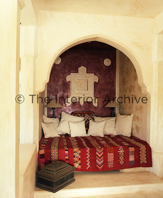 A daybed has been placed in an alcove in which one wall has been painted a deep maroon constrasting with the vibrant reds of the traditional kilim