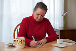 Woman at dining room table writing letters