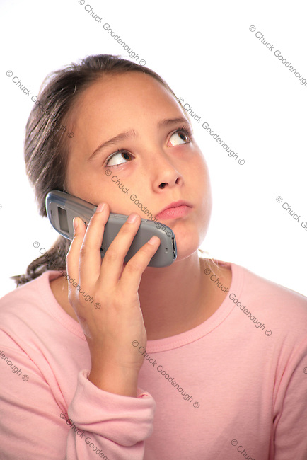 Photo of a teen girl talking and messaging on her mobile phone.
