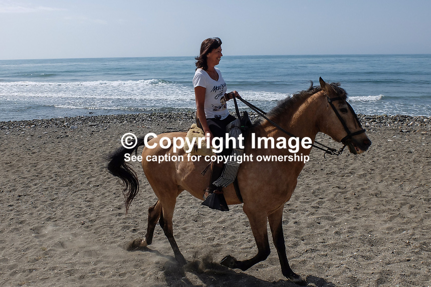 Horsewoman has a leisurely Sunday morning canter along the shore between Puerto Banus and San Pedro de Alcantara. April, 2017, 201704233487<br /> <br /> Copyright Image from Victor Patterson, 54 Dorchester Park, <br /> Belfast, UK, BT9 6RJ<br /> <br /> t1: +44 28 9066 1296 (from Rep of Ireland 048 9066 1296)<br /> t2: +44 28 9002 2446 (from Rep of Ireland 048 9002 2446)<br /> m: +44 7802 353836<br /> <br /> e1: victorpatterson@me.com<br /> e2: victorpatterson@gmail.com<br /> <br /> www.victorpatterson.com<br /> <br /> Please see my Terms and Conditions of Use at www.victorpatterson.com. It is IMPORTANT that you familiarise yourself with them.<br /> <br /> Images used on the Internet must be visibly watermarked i.e. &copy; Victor Patterson within the body of the image and copyright metadata must not be deleted. Images used on the Internet have a size restriction of 4kbs and will be chargeable at current NUJ rates unless agreed otherwise.<br /> <br /> This image is only available for the use of the download recipient i.e. television station, newspaper, magazine, book publisher, etc, and must not be passed on to any third party. It is also downloaded on condition that each and every usage is notified within 7 days to victorpatterson@me.com<br /> <br /> The right of Victor Patterson to be identified as the author is asserted in accordance with The Copyright Designs And Patents Act (1988).
