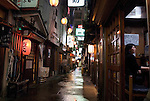"A customer enjoys a drink at one of the 47 bars along Nonbeiyokocho, or ""Drnkard's Alley"" in Shibuya, Tokyo. Customers wander past bars in the Golden Gai district of Shinjuku, Tokyo, Japan. Nonbeiyokocho began life immediately after World War II as group of tea houses. Though the alley is just a short walk from the central Shibuya shopping district, the rents are low due to the area being built over a river. Today 47 eateries, each with barely enough room to swing a cat, serve beer, fine wines and good, inexpensive fare."