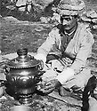 Iraq 1963 .A peshmerga preparing a little glass of tea in the field.Irak 1963.Un peshmerga se preparant une tasse de the