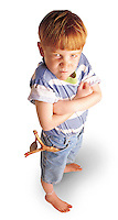 Portrait of young boy with a slingshot in his pocket and a mean look on his face.
