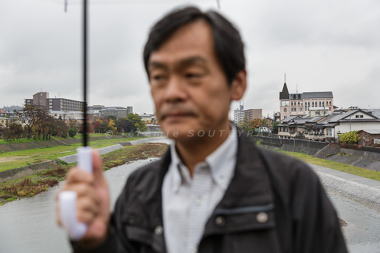 Kyoto, Japan, November 27 2016 - Mr KWAK Jinwoong, an activist for civil rights for zainichi population, in front of the river banks where Kyoto&rsquo;s zainichi community used to live in very poor condition, without eletricity or water. Mr KWAK&rsquo;s family members were born in Japan. Mr KWAK has South-Korean nationality and a passport, while his wife JONG Myong Ae, 46, kept the &laquo;&nbsp;chosen&nbsp;&raquo; japanese status which means she technically has no valid passport and a lot of difficulties to travel. She owns 2 documents: a 2 year temporary passport issued by DPRK authorities when she traveled to Pyiongyang at the age of the 18 and a &laquo;&nbsp;travel certificate&nbsp;&raquo; issued by South Korea with no international validity.<br /> The majority of Koreans in Japan are Zainichi Koreans, often known simply as Zainichi , who are the permanent ethnic Korean residents of Japan. The term &quot;Zainichi Korean&quot; refers only to long-term Korean residents of Japan who trace their roots to Korea under Japanese rule, distinguishing them from the later wave of Korean migrants who came mostly in the 1980s. The estimated population is about 500,000 people. As of 2016, about 90% of them have South Korean nationality and 10% of them are considered by Japanese administration as &laquo;&nbsp;Korean&nbsp;&raquo; (chosenjin), the word used for korean people before the division between North and South Korea in 1948. The ratio used to be the opposite in the 1950ies.